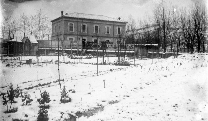 Vista general dels terrenys davant de l'antiga estació de tren, amb el quiosc de begudes al costat dret de l'edifici, 1928 (ACGAX. Fons Sadurní Brunet Pi. Autor: Sadurní Brunet)