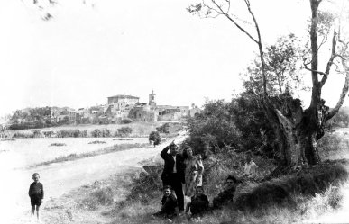 Retrat de grup de cos sencer als afores de Sant Mori. Al centre, assenyalant enlaire, Sadurní Brunet Pi i, al seu costat, la seva filla Conxita. Al fons, el poble amb les siluetes destacades de la torre del campanar de l'església de Sant Maurici i el castell de Sant Mori, 1946 (ACGAX. Fons Sadurní Brunet Pi. Autor: Sadurní Brunet)