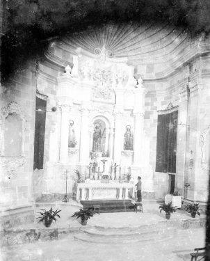 Altar major de l'església de Santa Eulàlia de Noves, a Garriguella, amb Jordi Brunet Forasté al davant, 1941 (ACGAX. Fons Sadurní Brunet Pi. Autor: Sadurní Brunet)
