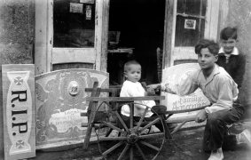Retrat de tres nens davant el taller del carrer de Santa Magdalena, 10, a Olot; en primer terme Sadurní Brunet Forasté i damunt del carretó el seu germà Jordi, 1928 (ACGAX. Fons Sadurní Brunet Pi. Autor: Sadurní Brunet)