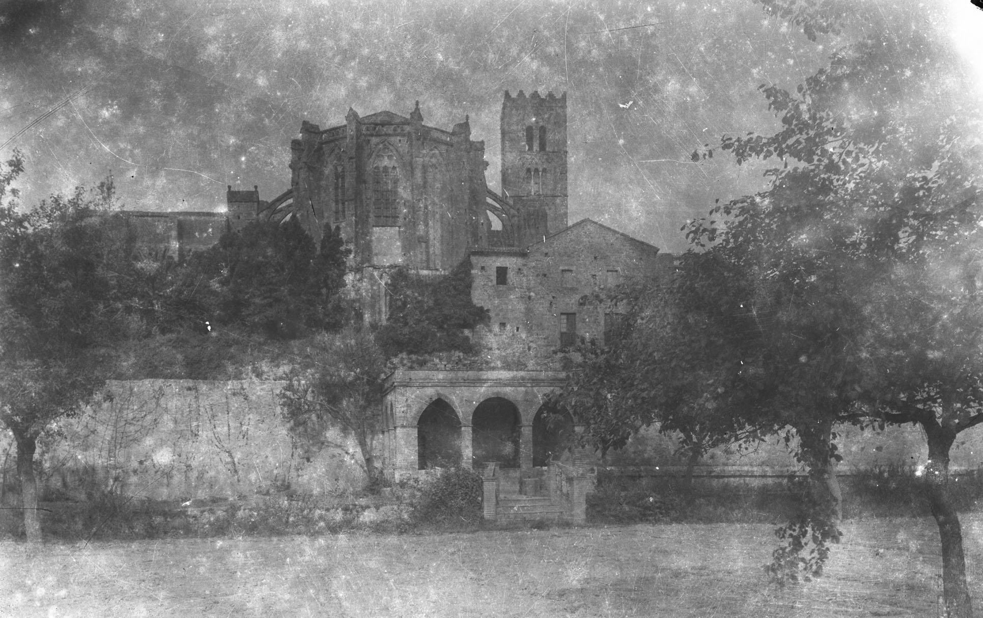 Vista parcial de Castelló d'Empúries. Al centre, l'absis central i la torre del campanar de la basílica de Santa Maria, entre els anys 1942 i 1944 (ACGAX. Fons Sadurní Brunet Pi. Autor: Sadurní Brunet)