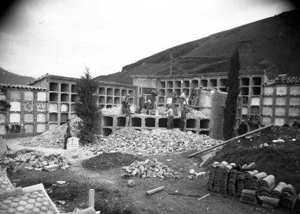 Vista general del Cementiri d'Olot amb treballadors enderrocant nínxols, c. 1933 (ACGAX. Fons Sadurní Brunet Pi. Autor: Sadurní Brunet)