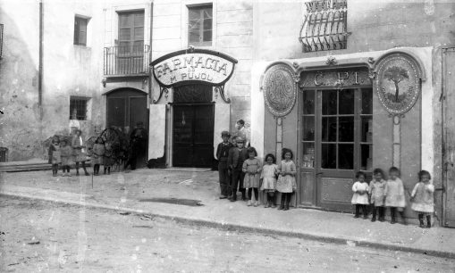 Vista frontal de la farmàcia Pujol i la xocolateria Pi, a Tortellà, 1917, (ACGAX. Fons Sadurní Brunet Pi. Autor: Sadurní Brunet)