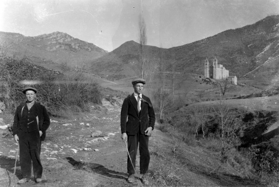 Retrat de dos homes amb l'església del Remei de Creixenturri de Camprodon al fons, c. 1950 (ACGAX. Fons Sadurní Brunet Pi. Autor: Sadurní Brunet)